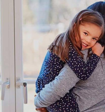 Mãe com a sua linda filha ao colo - uma criança concebida com esperma de doador do banco de esperma da Cryos