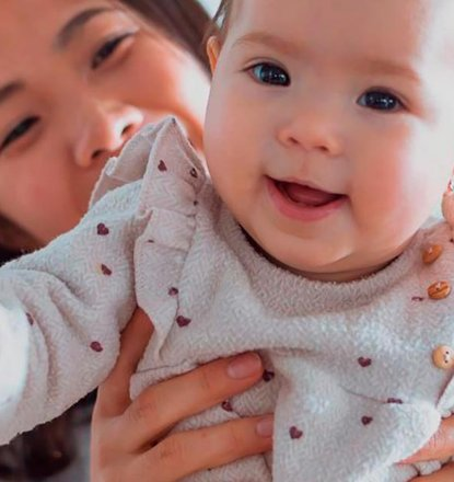 妈妈抱举着通过使用Cryos捐献者精子出生的漂亮的小宝贝