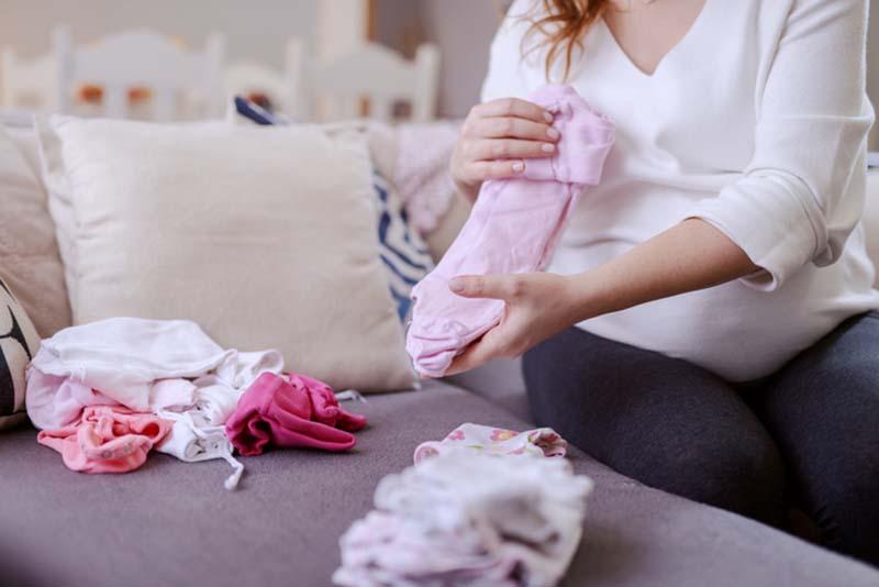 Alenemor der folder tøj til sit kommende barn