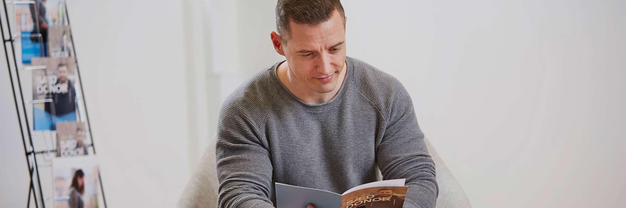 Mand læser om hvordan man bliver sæddonor hos Cryos