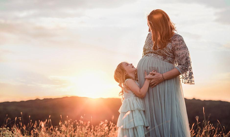 Κόρη αγκαλιάζει τη μητέρα της, που είναι έγκυος μετά από θεραπεία γονιμότητας με κρυοσυντήρημένα ωάρια