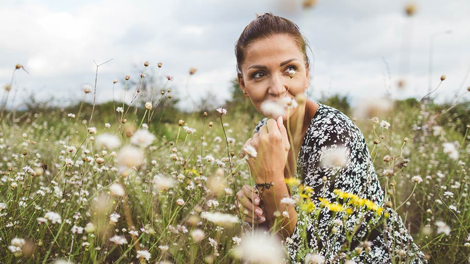 Young woman in flower field considering egg freezing at Cryos