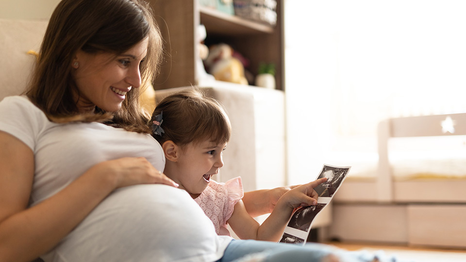 Mother and child looking at picture of future sibling – reserve donor eggs for siblings