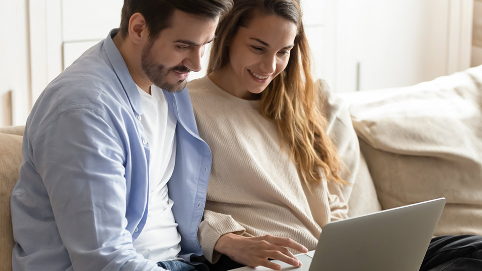 Couple with computer calculating the price of donor eggs from Cryos