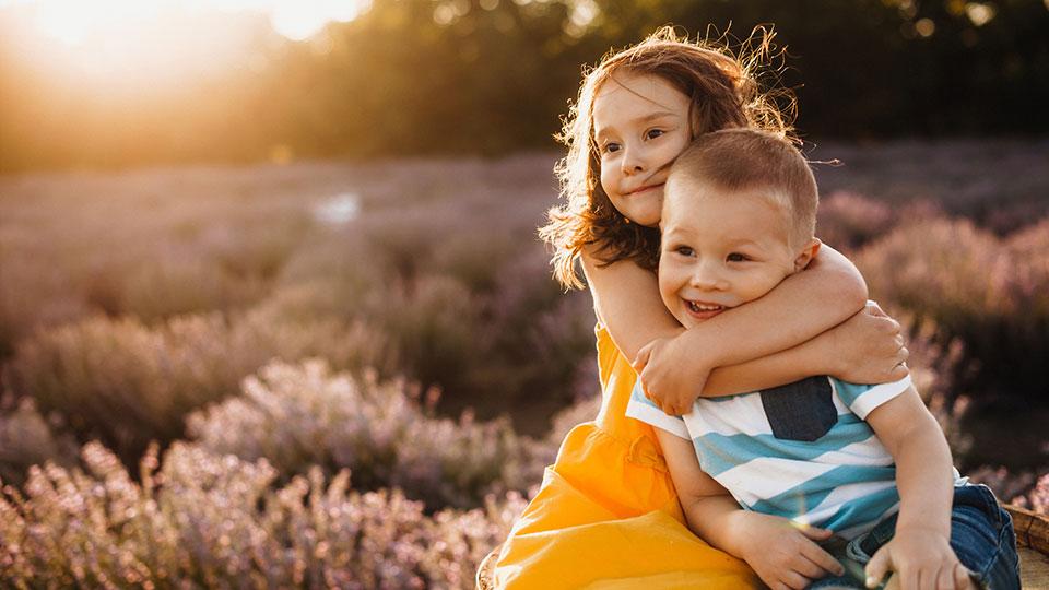 Genetic siblings from same egg donor hugging