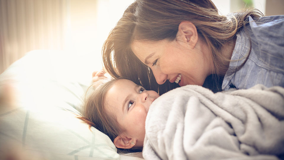 Mother and daughter in bed talking about possible contact with an egg donor