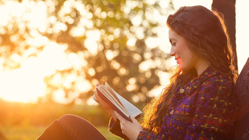 Young woman reading in the park – learn about Cryos' egg donor profiles