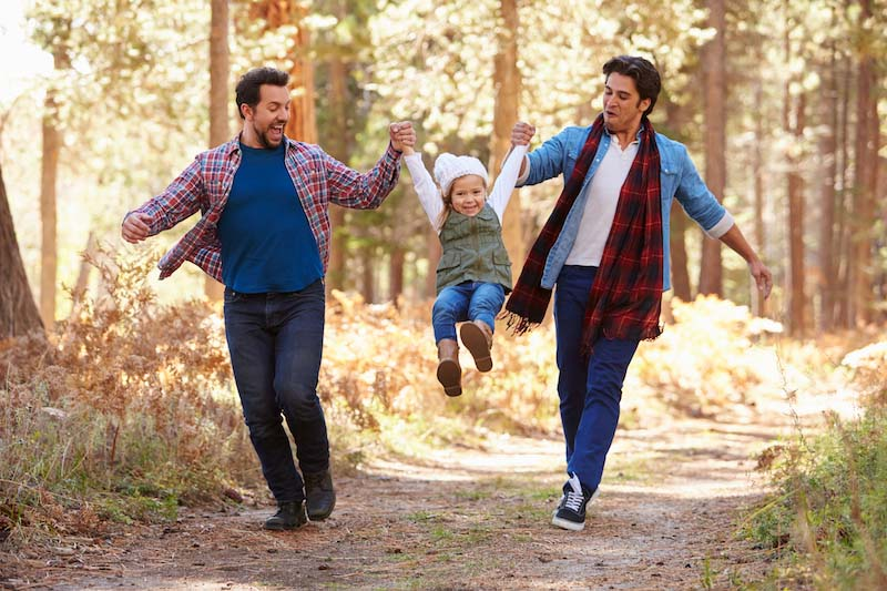 Two dads and their child playing in the forest