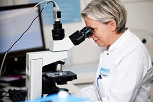 Woman lab technician looking at sperm cells through a microscope – Photo from the Cryos press kit.