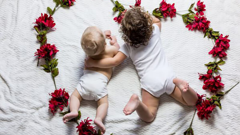 Happy Mother's Day and some tips for coping through the day for those struggling with infertility from Cryos International Sperm and Egg Bank - two babies in a heart made of flowers