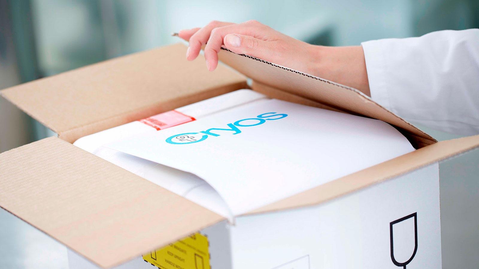 Empleado de Cryos preparando una caja de hielo seco para el envío de esperma de donante a un cliente