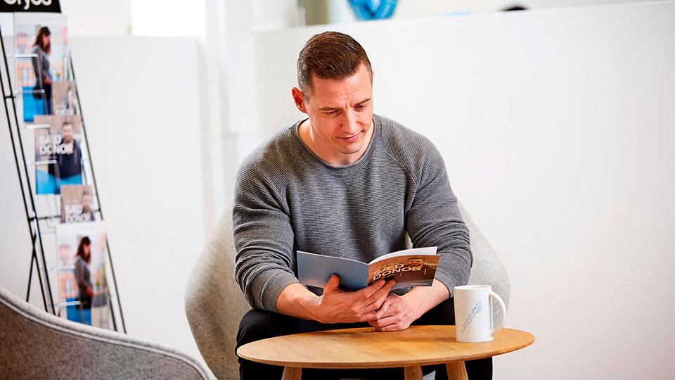 Donante de esperma leyendo sobre los tipos de perfil de donantes en Cryos