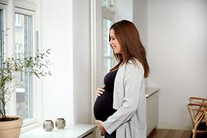 Une femme enceinte tenant son ventre – Photo du dossier de presse de Cryos.