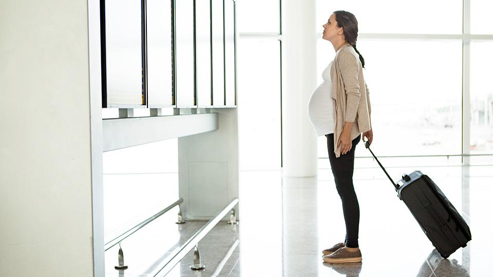 Une femme avec une valise, voyageant à l'étranger pour suivre un traitement de fertilité