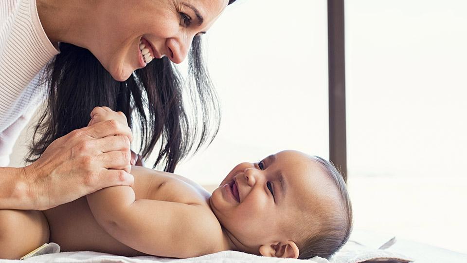 おむつを替えながら、お子さんの誕生ストーリーを語りかける母親