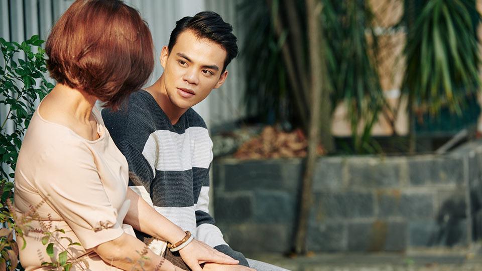 ドナーと連絡を取る前に母親と相談する若い男性