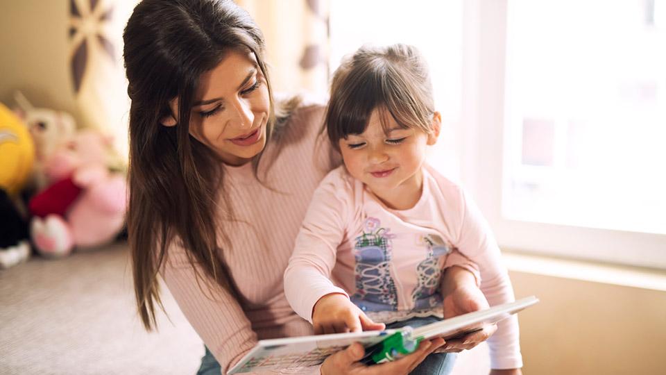 Moeder en dochter die een kinderboek lezen over donorconceptie
