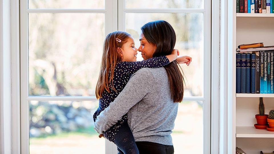 Mulher solteira por opção a abraçar a sua filha concebida através de um doador