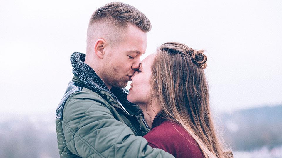 Casal infértil a beijar-se e a pensar em ter uma criança utilizando o esperma de um doador para conceber a criança